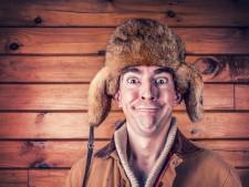 un hombre con sonrisa boba con un gorro de piel, al fondo una pared de madera